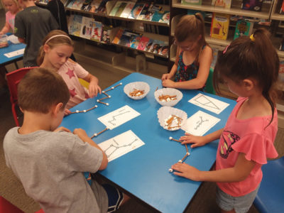 Children make constellations crafts out of pretzels and marshmallows