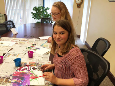 Teens making blow art paintings during a craft club
