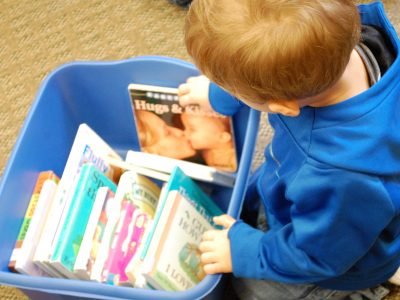 toddler with book bin